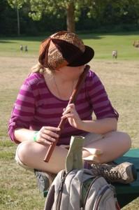 La fille avec une flûte et un chapeau